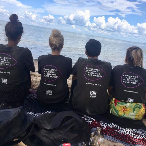 Four VSO ICS volunteers sat on the floor wearing t-shirts with text saying 'Challenge yourself to change your world'